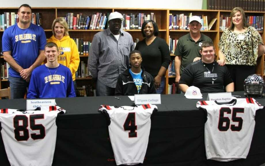 Trojan football players kick off National Signing Day as they sign letters of intent at a signing ceremony held at the Coldspring-Oakhurst High School Library on Wednesday, Feb. 6. Shown left to right are Casey Lilley, Jerrell Sykes and Jake Mizell. Standing with the young men are their parents.