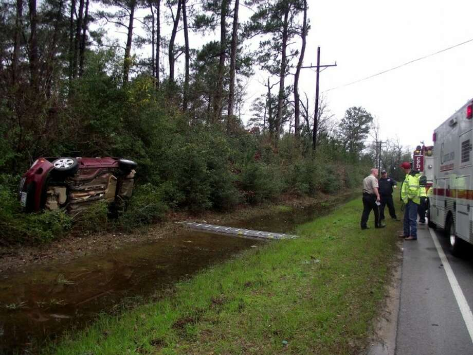 "Cleveland firefighters placed a ladder across the ditch for Vernie ""Bubba"" Mikels to cross after he climbed out of his wrecked vehicle on FM 2025 Friday, Feb. 10. Mikels flipped the 2007 Chevy HHR after losing control of the vehicle around a sharp curve in the road that was slick from poor weather conditions."