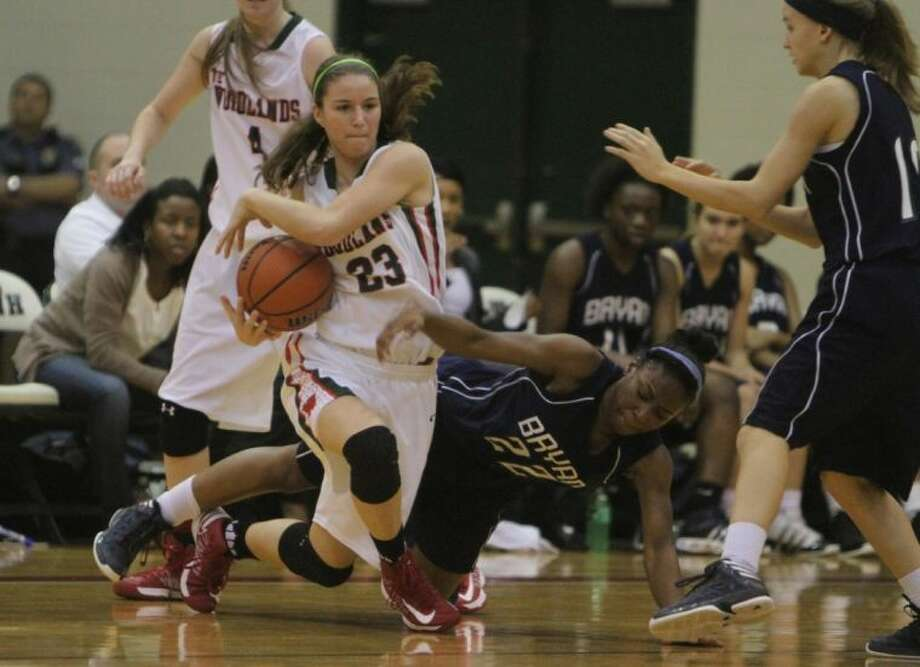 The Woodlands forward Payton Walker grabs a loose ball from Bryan's Penny Watson on Tuesday night at The Woodlands High School. The Lady Highlanders won 58-41 to complete an undefeated 12-0 run to the District 14-5A title. The Woodlands is 27-7 overall and opens postseason play next week.