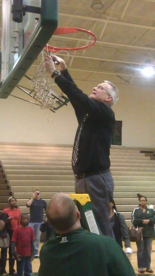 Cy Falls girls basketball coach Jim Stephens cuts down the net after winning the District 17-5A championship Tuesday night. Photo: Adam Coleman
