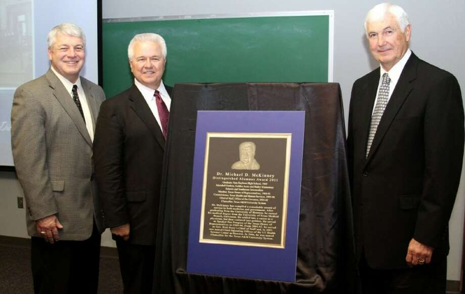 Dr. Mike McKinney, flanked by Pasadena ISD Superintendent Dr. Kirk Lewis and School Board Vice President Marshall Kendrick, poses next to a mockup of his Distinguished Alumnus plaque, to be placed on permanent display outside the Administration Building.