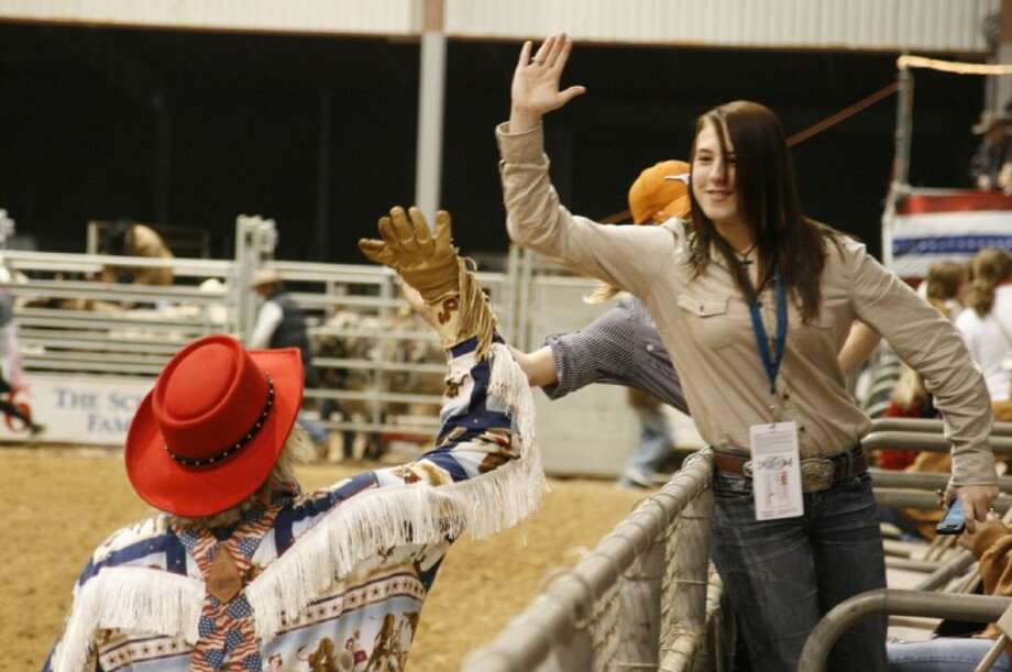 One of the rodeo clowns gave out high fives to the audience before the start of the festivities at the Humble Rodeo Feb. 10.