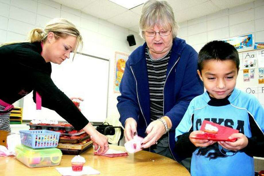 Holly Sewell (left), assisted by Shepherd Primary School (SPS) first grade teacher Cindy Lumus (center), serves a cupcake to first grade student Christian Castillo. Sewell was one of 17 people who came to speak to SPS students on Wednesday, February 10, as part of a career day.