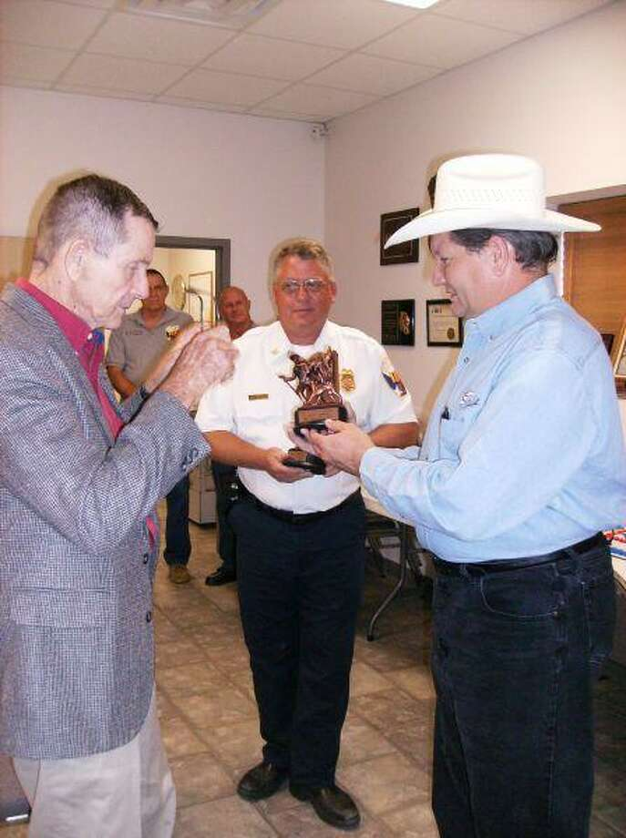 Crash survivor Bill Philpot, 70, of the Grangerland area, presents Perry Orrick, 45, with a New Caney Fire District Lifesaver award at an Aug. 26 ceremony attended by family and friends at the New Caney Fire Department.