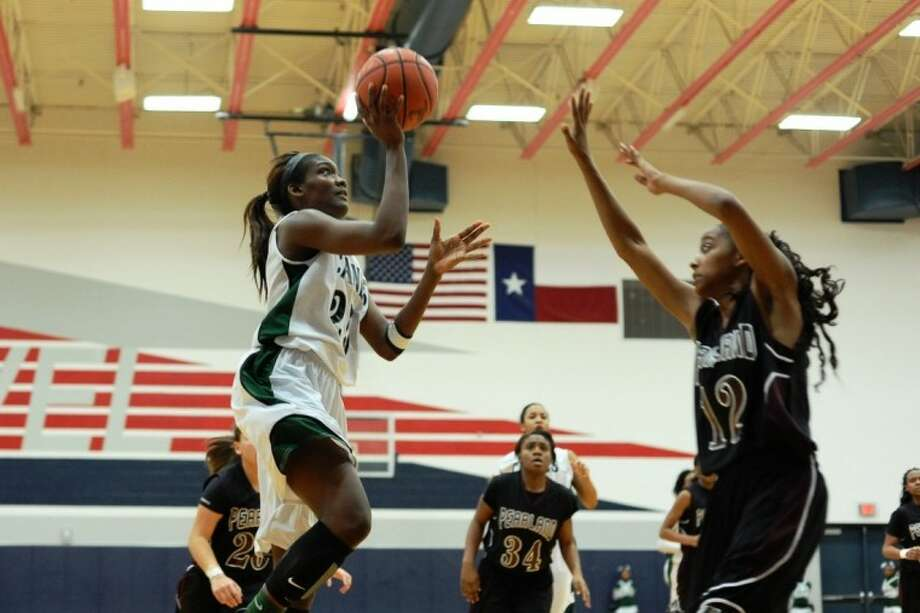 Hightower's Jasmine Prophet launches a shot over Pearland's Taylor James Tuesday in a Class 5A girls' bi-district basketball playoff. Hightower cruised to a 59-41 win. Photo: KIRK SIDES