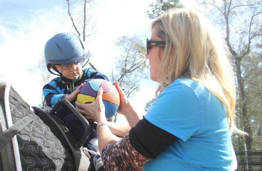 Three-year-old Cody Buchanan works on hand-eye coordination with Linda Darnall, founder of Panther Creek Inspiration Ranch, during a session on Jan. 31, in The Woodlands. Buchanan, who has cerebral palsy, has been receiving therapy to help with his walking and hand-eye coordination through the assisted therapeutic riding for the last year. The program helps 50 kids overcome their physical and mental disabilities using horses and other activities. Photo: Jason Fochtman
