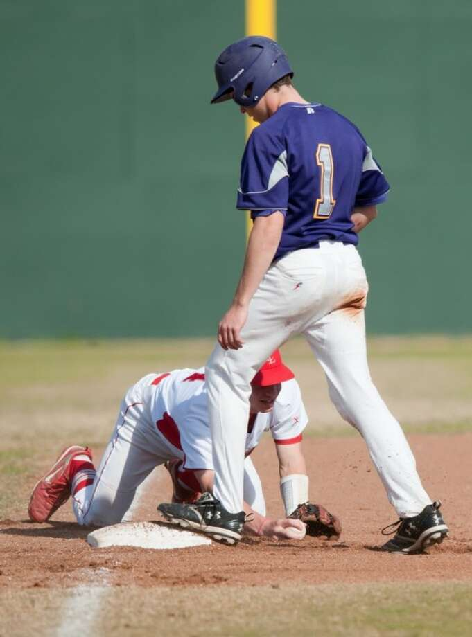 Kinkaid outfielder Forbes Dumas puts his foot on third base while an infielder clutches the baseball.