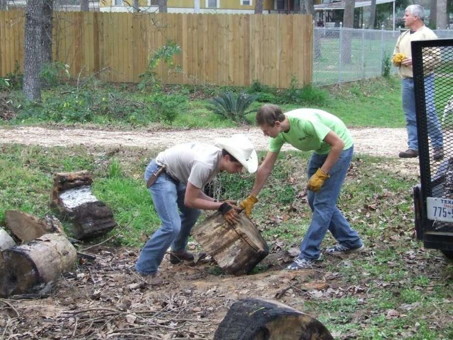 Jesse McCorkle, left, and Joey Bailey with Boy Scout Troop 113 in Tomball move tree stumps on Saturday morning as part of a service project.