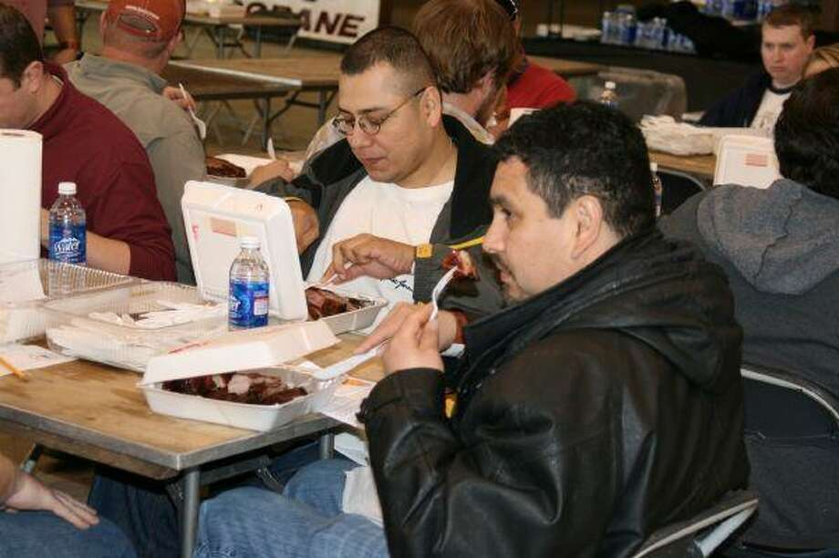 A judge smells the flavors of the meat before sampling a taste during the judging portion of the Humble Rodeo barbecue cook-off Feb. 6.