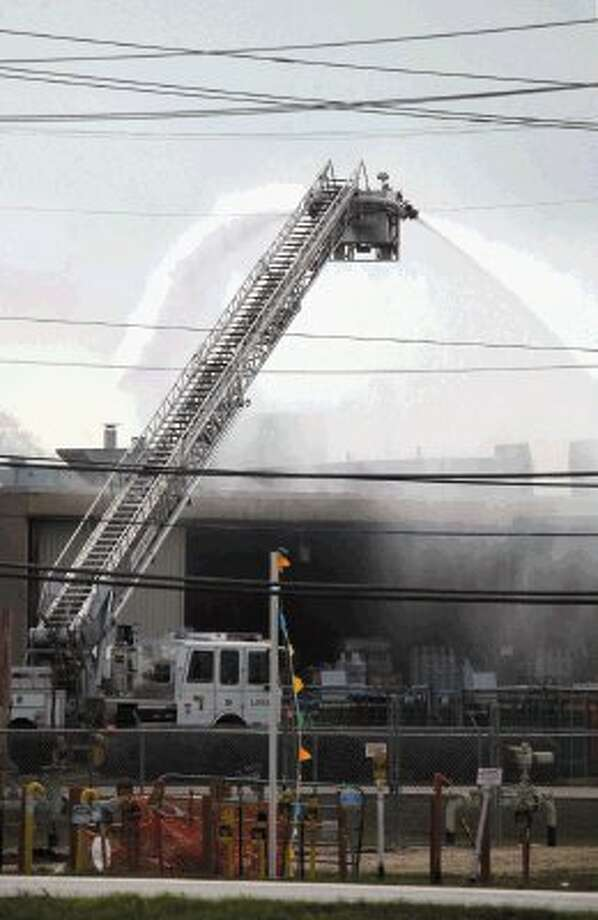 Firefighters use a ladder truck to put water on the fire at Air Liquide in La Porte. Photo: Kar B Hlava