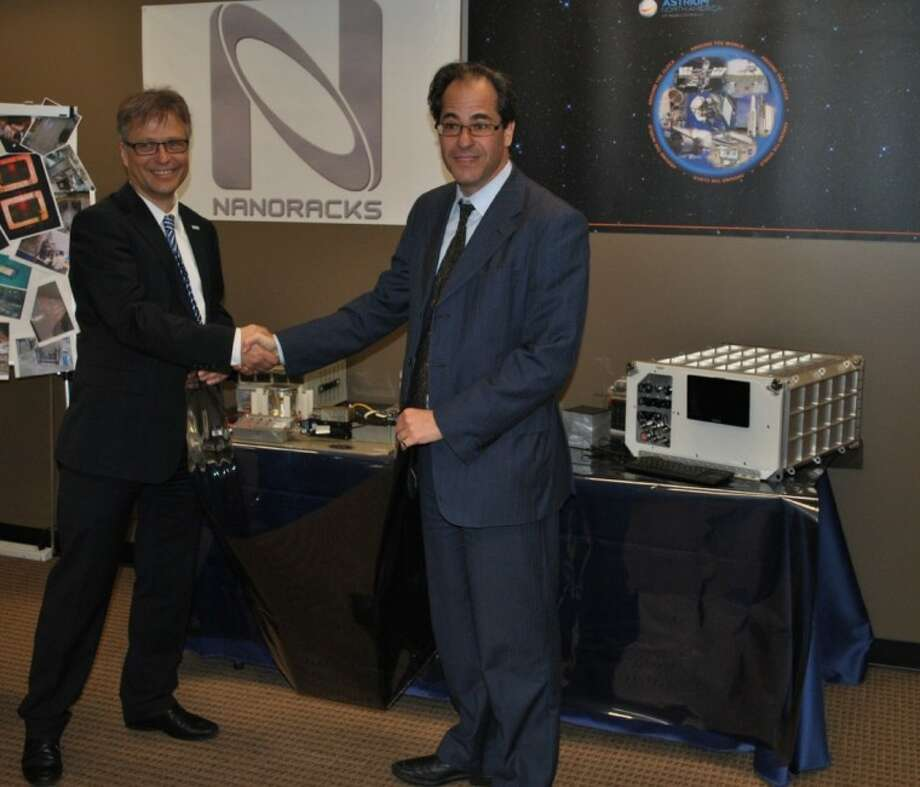 Ulrich Kuebler, head of Astrium's ISS Utilization Office, left, and NanoRacks Managing Director Jeffrey Manber unveil the two companies' centrifuge facility to be used on the International Space Station.