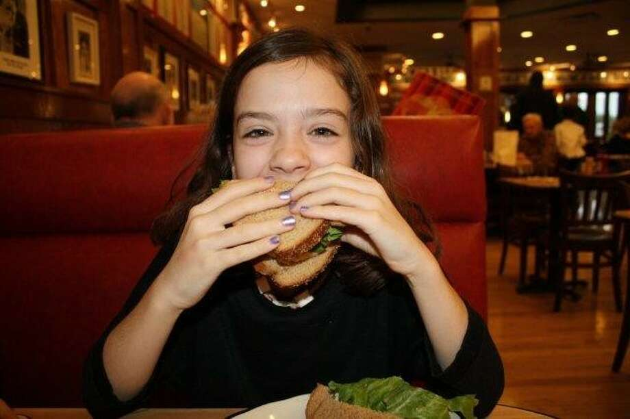 Eight-year-old twins Charlotte and Kate Durham can't agree much when it comes to menus, but they both came away with smiles after filling their tummies at Kenny & Ziggy's on Post Oak Boulevard. Pictured: Charlotte loves her big tuna sandwich.