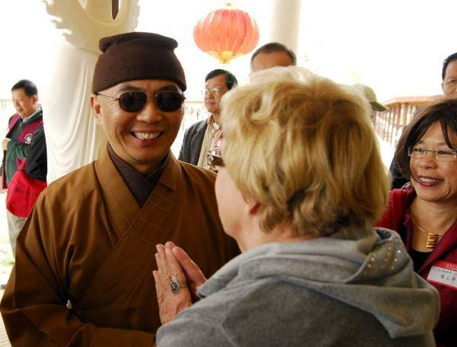 The Rev. Hung I greets visitors Saturday to the American Bodhi Center for the Chinese Lunar New Year celebration.