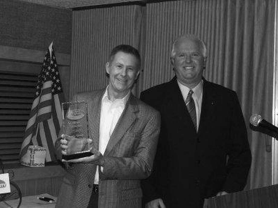 John Keating, left, of John Keating Chevrolet in Crosby receives the Business of the Year Award, presented by Mike Godsey, from the Crosby Huffman Chamber of Commerce.