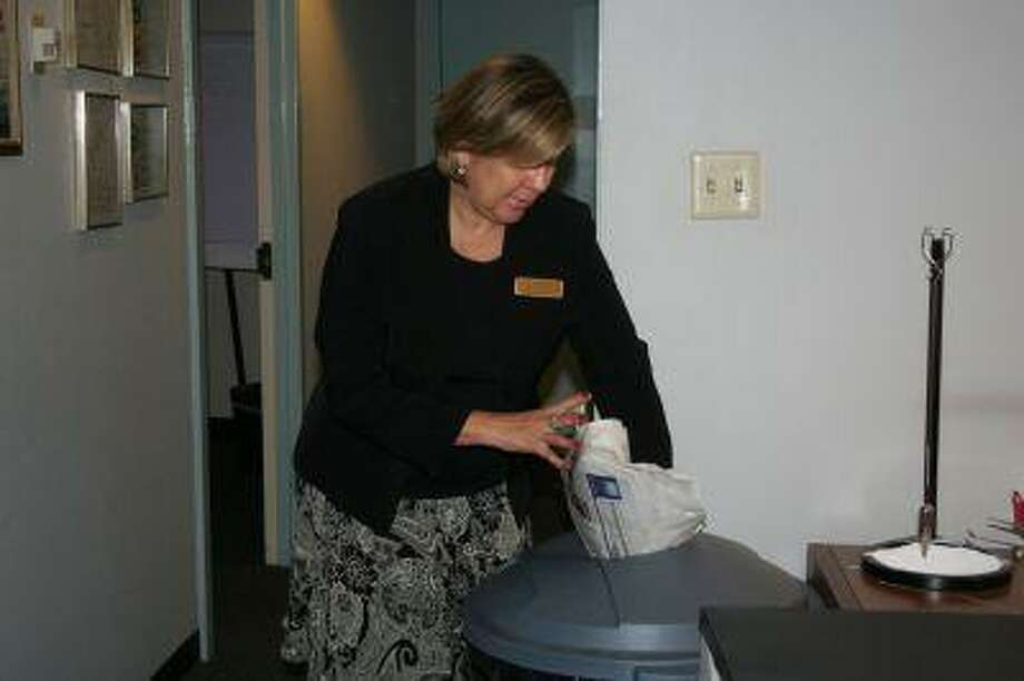 Linda Cahue, director of sales and marketing at the Houston Airport Marriott at George Bush Intercontinental, recycles a newspaper as part of the hotel's initiative to stay green.