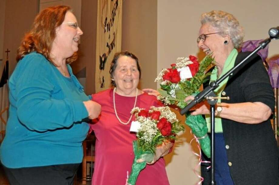 Pat Malinak, left, Governing Board Secretary surprisesBetty Frazier Assistant Executive Director and Jean Wottrich, Executive Director of Pasadena Community Ministry with beautiful bouquets of roses. Photo: JACKIE WELCH
