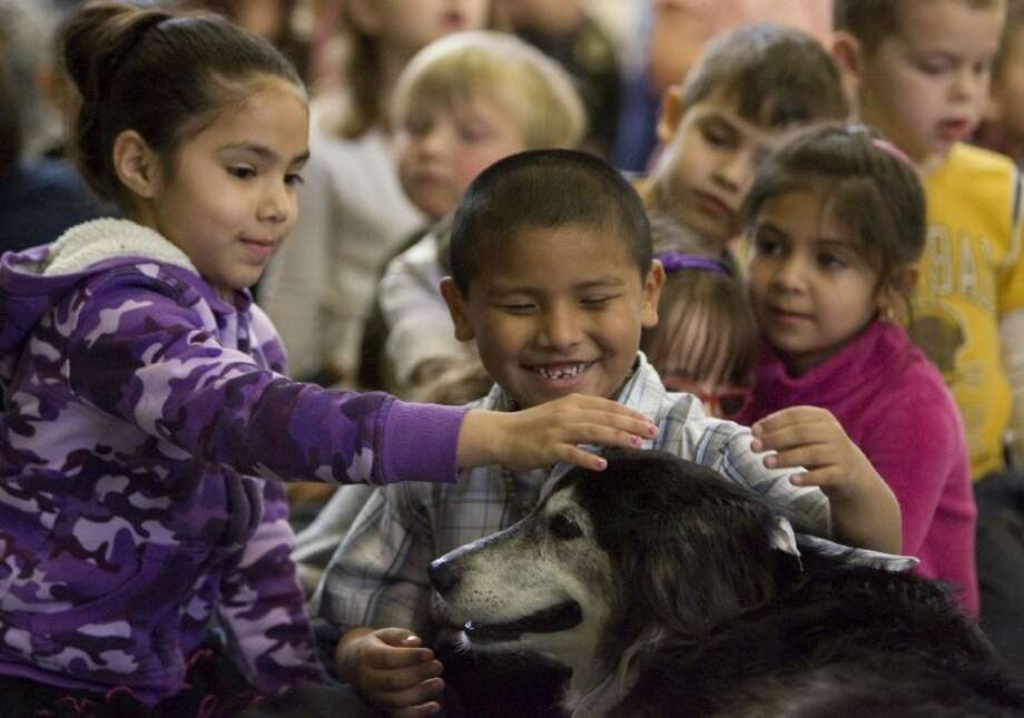 Glen Loch Elementary School students pet Suki during the Dogs of Character assembly at the school last week. Photo: Staff Photo By Eric S. Swist