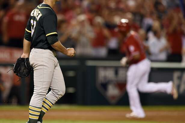 Oakland Athletics starting pitcher Daniel Mengden, left, reacts after allowing a grand slam to Los Angeles Angels' Jefry Marte, right, during the fourth inning of a baseball game in Anaheim, Calif., Tuesday, Sept. 27, 2016. (AP Photo/Kelvin Kuo)
