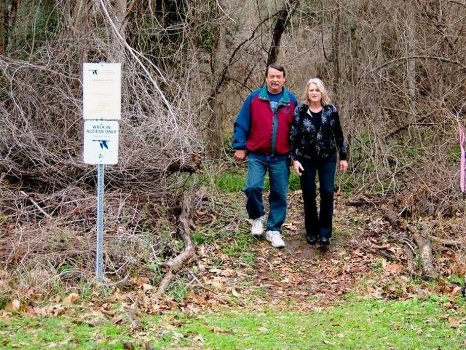 Ken and Kathy Doan of Liberty exit the Knobby Knees Trail in the Liberty municipal park. The trail connects to the Trinity River National Wildlife Refuge. Photo: CASEY STINNETT