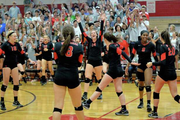 Memorial players celebrate their 3-0 victory over Stratford following the third set of a high school volleyball game between the Memorial Mustangs and Stratford Spartans on September 27, 2016 at Memorial High School, Houston, TX.