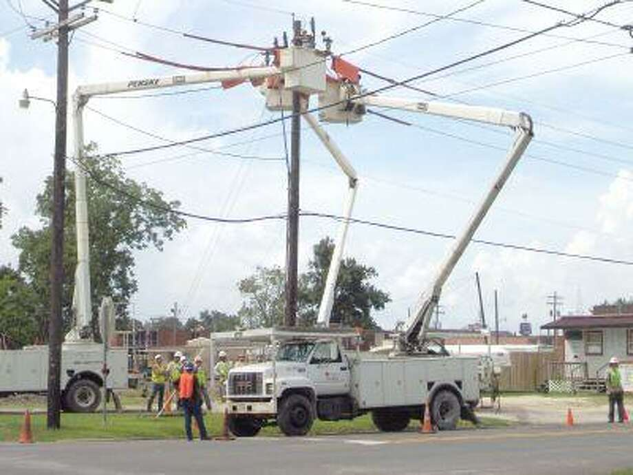 Entergy work crews work at the corner of Clayton and Winfree to ensure continued service on lines the day following Tropical Storm Eduard. Line and tree-trimming crews spent the rest of the week working in and around Dayton as well as other areas affected by the storm.