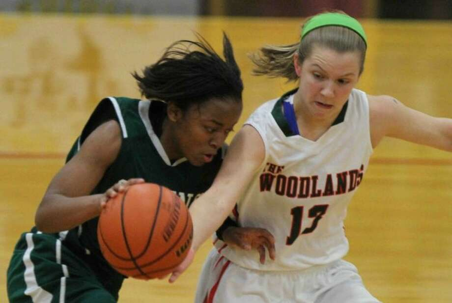 The Woodlands guard Jessica Hill (13) tips the ball as Spring guard Brittany Smith (23) dribbles upcourt during a bi-district high school playoff game at Klein Oak High School. The Woodlands defeated Spring 67-38. Go to HCNPics.com to purchase this photo and others like it.