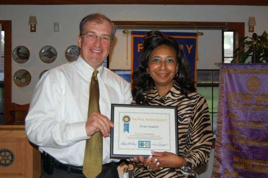 EMC Rotary President Tim Baker presents Rose Austin her Paul Harris Society award during the luncheon April 28.