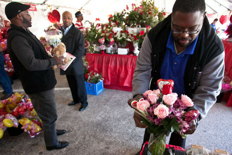 Humble Kroger employee James Bass prepares a vase of flowers for Spring resident Byron Williams on Valentine's Day, February 14, 2013.