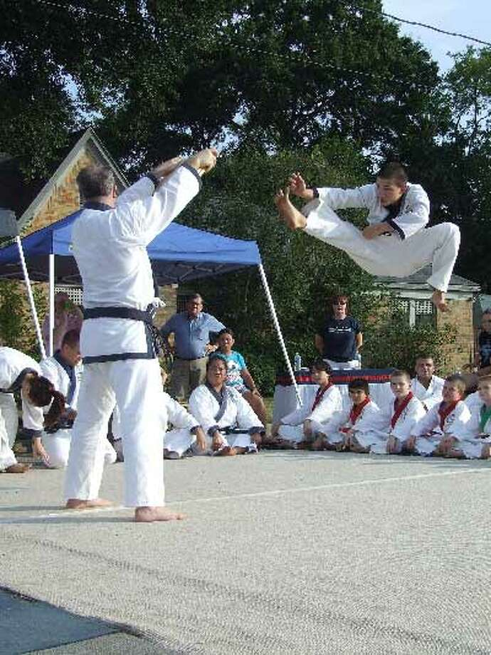 A martial artist with Soo Bahk Do Moo Duk Kwan in Tomball jumps to break a wood board with his foot. The demonstration was conducted by the martial arts studio during Tomball Night, Aug. 1.