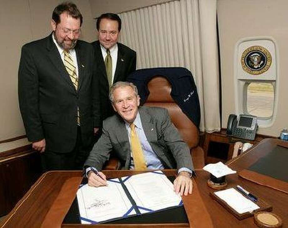 President Bush signs the Clean Boating Act aboard Air Force One last week. With him are, left, Representatives Steven C. LaTourette (R-OH) and Patrick Tiberi (R-OH).