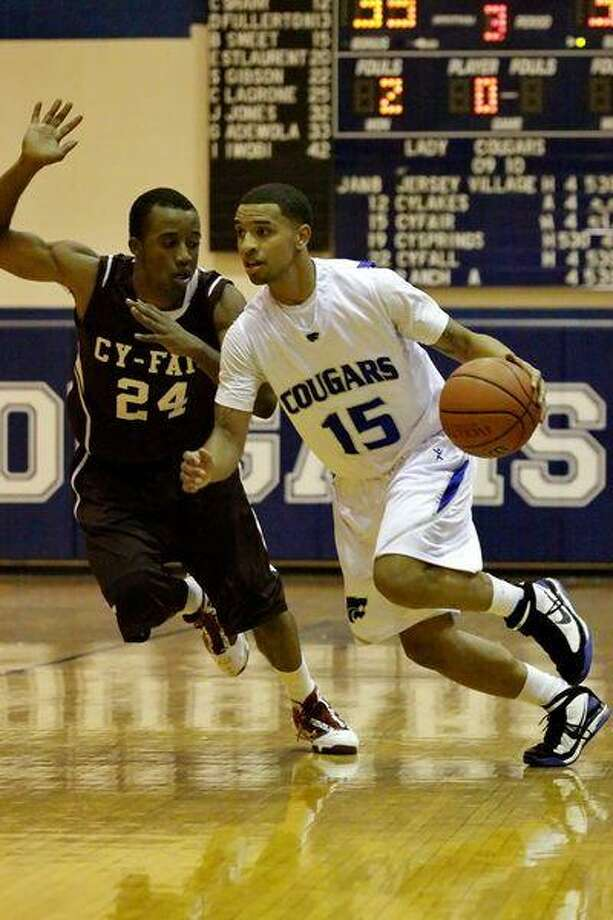 Cy Creek High senior guard Robert Goffney, right, drives to the basket against Cy-Fair senior guard Lawrence Paye during the Cougars' 64-54 victory over Cy-Fair last Friday. (Photo by kjwesphotos.com)