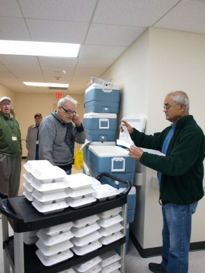 Monday's program coordinators, Al Smith and Amal Bhattacharya, collect warm meals at Christus St. John Hospital before the volunteer group heads out on their routes. This year marks Bay Area Meals on Wheels' 30th year serving the community.