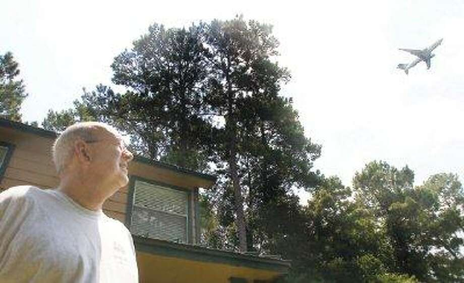 Humble resident Rick Dickson watches a plane fly over his home on North Hollow Circle. / @WireImgId=340003