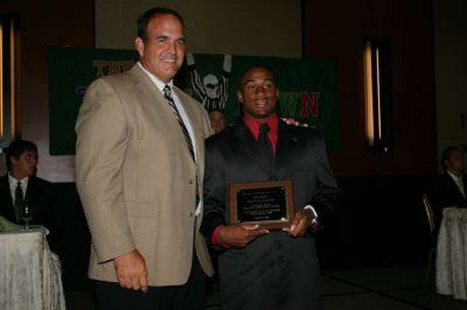 Kalvin Guyton collects a pre-season plaque for his outstanding running from Football Hall of Famer Bruce Matthews.