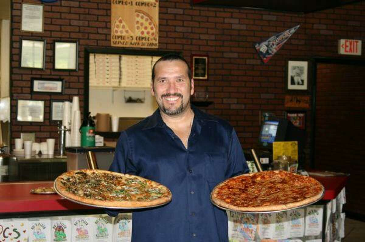 R.C. Gallegos shows off two of his signature pizzas including the traditional cheese pizza, right, which won the Best Tradtional Pizza for the South Central Region at the International Pizza Expo in Las Vegas.