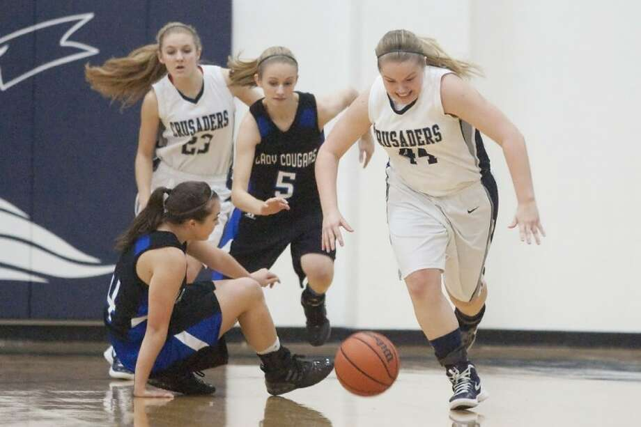Concordia Lutheran's Katelyn Holland steals the ball from Arlington Grace Prep's Rebekah Provines Friday at Concordia Lutheran High School. The Crusaders won the TAPPS Area Round playoff game 49-25 to advance to Saturday's Regional round needing just one victory for a fifth consecutive trip to the TAPPS 4A state tournament. See more photos online at www.yourconroenews.com/photos. Photo: Karl Anderson