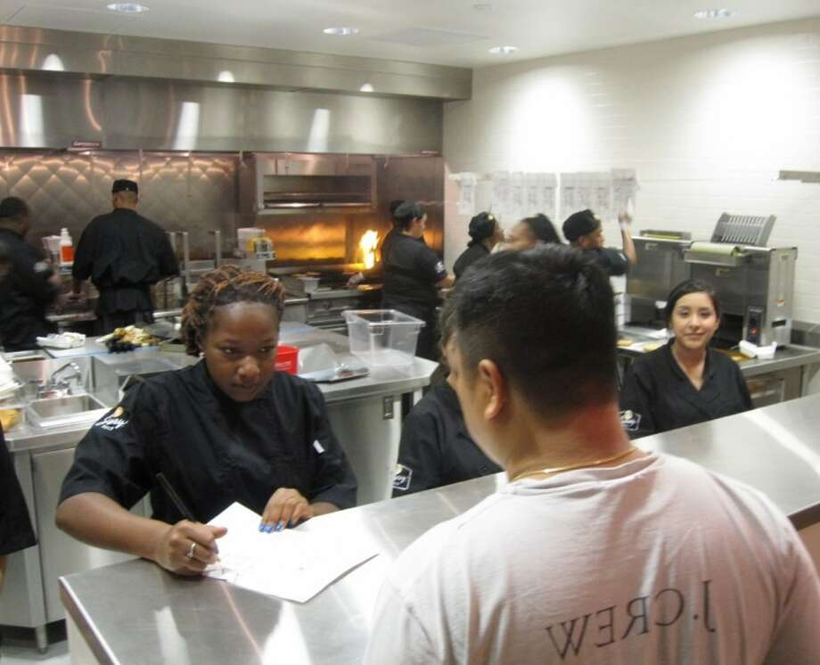 A customer places his order at a test-run Thursday night, as workers prep food in the background. Photo: CHARLOTTE AGUILAR