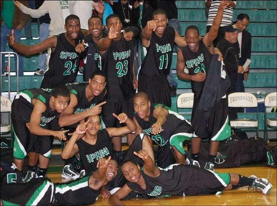 The Lions celebrate after beating Oak Ridge High School 60-51.