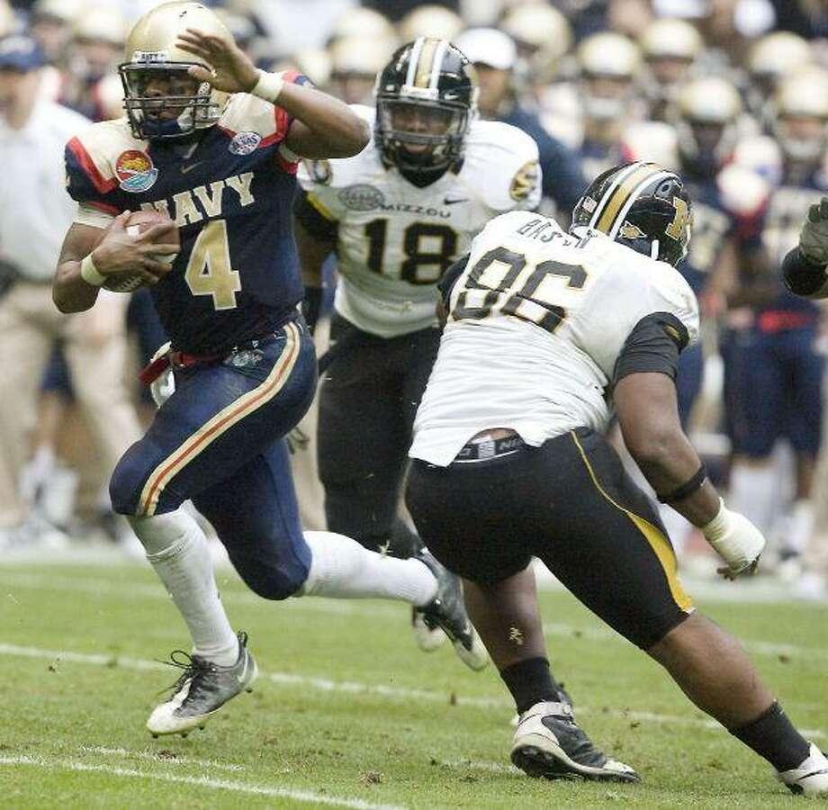 Midshipmen quarterback Ricky Dobbs (4) carries the ball through Missouri linemen Marcus Malbrough (18) and Jaron Baston.