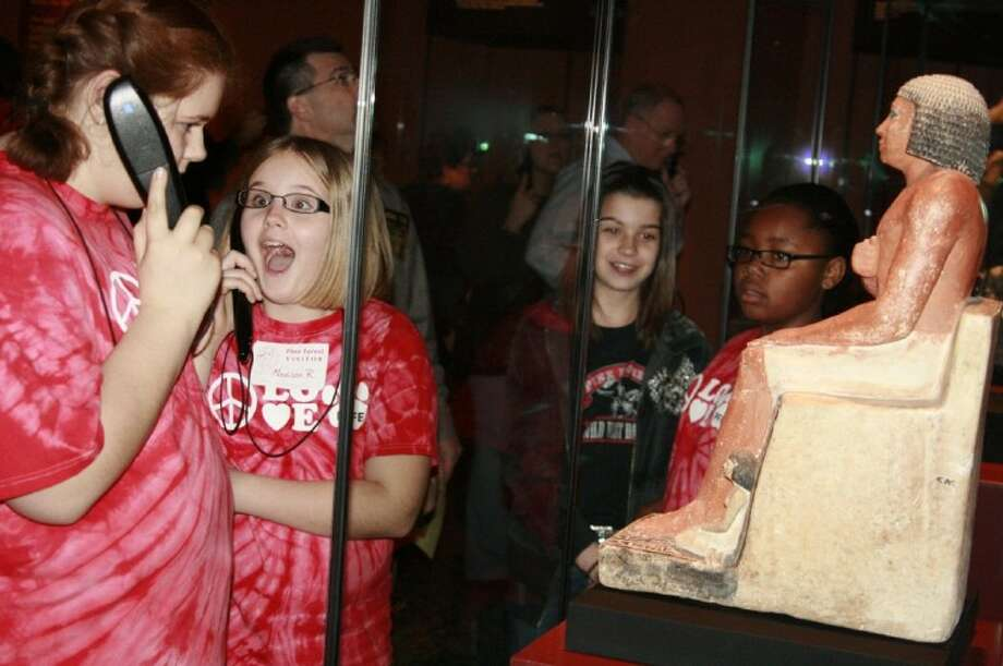 "Several Pine Forest Elementary students check out ancient Egyptian artifacts in the MFA-H exhibit ""Tutankhamun: The Golden King and the Great Pharaohs"" and listen to the audio devices which tell what that item is during their visit Feb. 17."