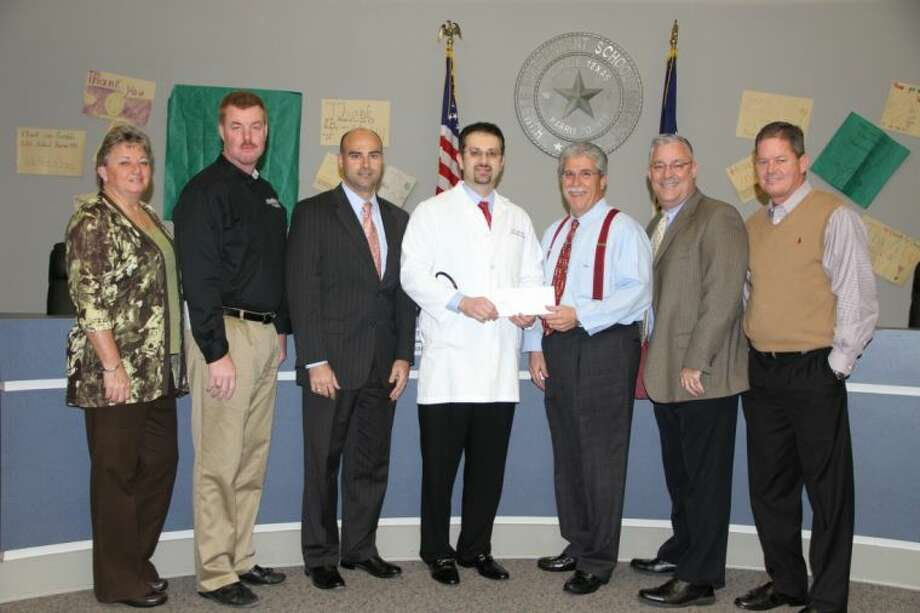 Cardiologist Charlie Gnaim, M.D. (fourth from left) present a $4,000 check to Dr. Guy Sconzo, Humble ISD Superintendent. Also pictured (from left) are: Krista Malmstrom, Humble ISD co-athletic director; Robert Maniscalco, Memorial Hermann outreach athletic trainer; Memorial Hermann Northeast Hospital Chief Operating Officer Heath Rushing; Dr. Gnaim; Dr. Sconzo; Trey Kraemer, Humble ISD assistant superintendent for secondary schools and athletics; and Troy Kite, Humble ISD co-athletic director.