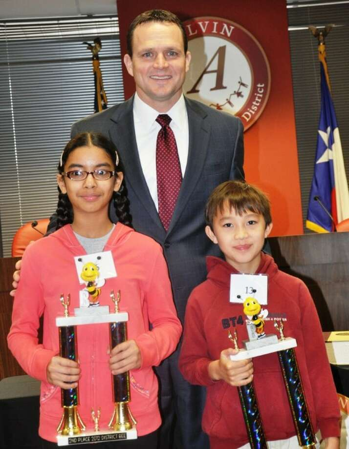 District Spelling Bee champion Dean Zach of York Elementary and runner up Ria Singh, of Wilder Elementary are pictured with Dr. Fred Brent, Superintendent of Alvin ISD. Photo: AISD
