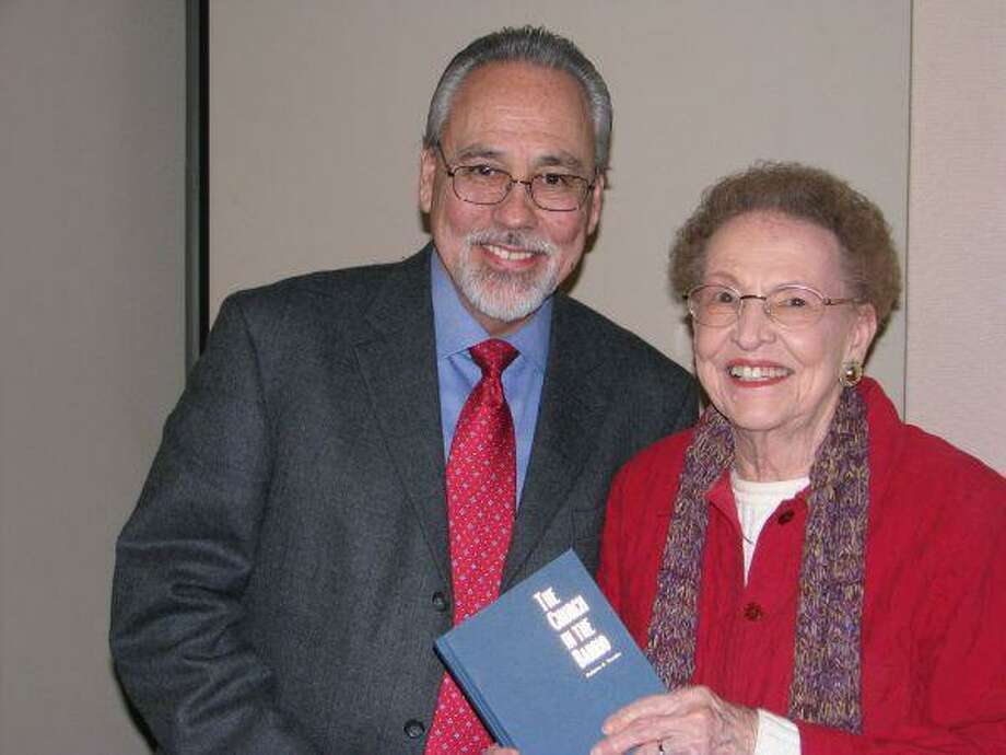 "Dr. Robert Trevino presents a signed copy of his book ""The Church in the Barrio"" to Jeanette DeFee of the Panarama Roundtable of Conroe."