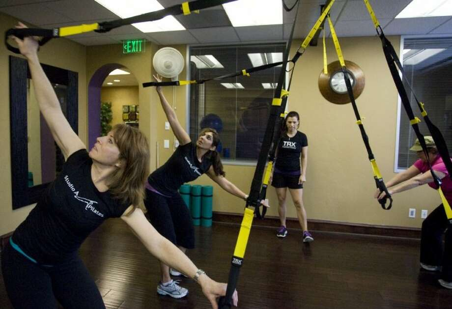 Fitness instructor Anna Gammill with Studio A Pilates looks on as clients workout using the TRX suspension training system during a class Thursday at Market Street The Woodlands.