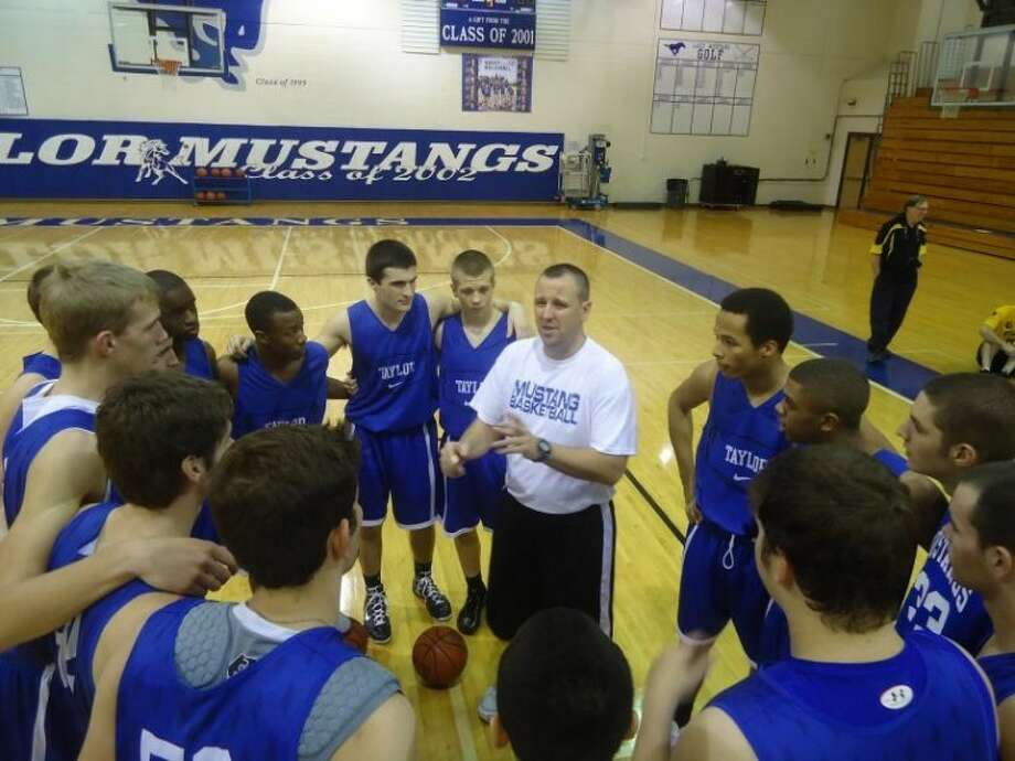 The Katy Taylor boys' basketball team huddles around head coach Matt Brayton after a practice last year. Getting in the playoffs this year has changed the atmosphere around the program. Photo: FILE PHOTO