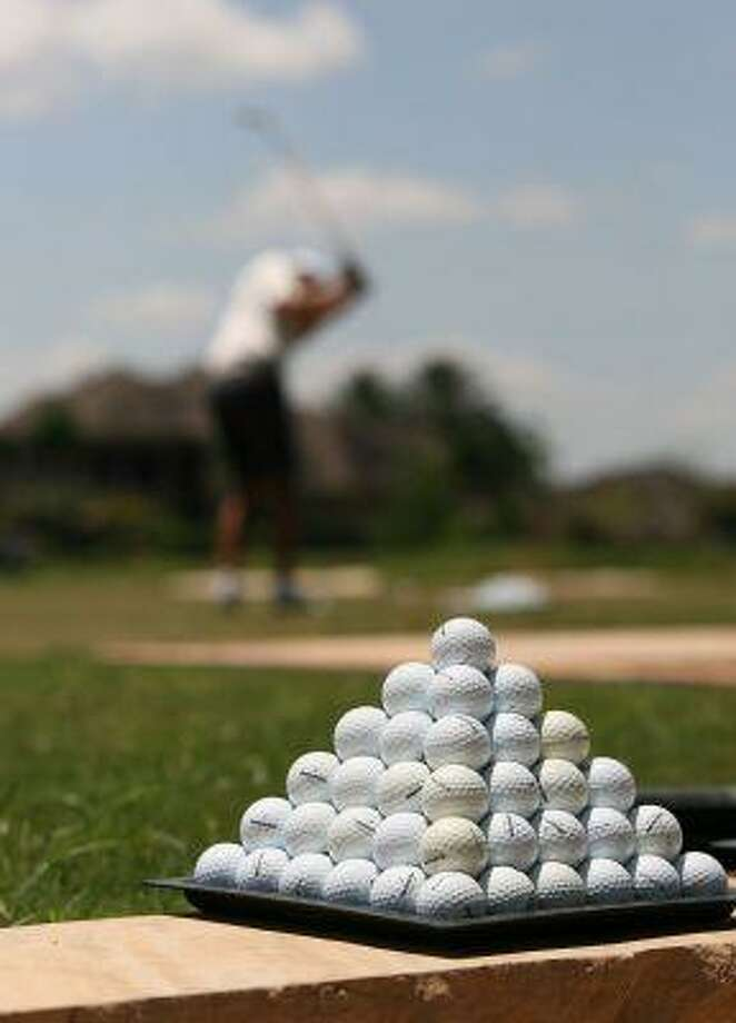 A golfer tees off in the background as a pyramid of golf balls await the next player.