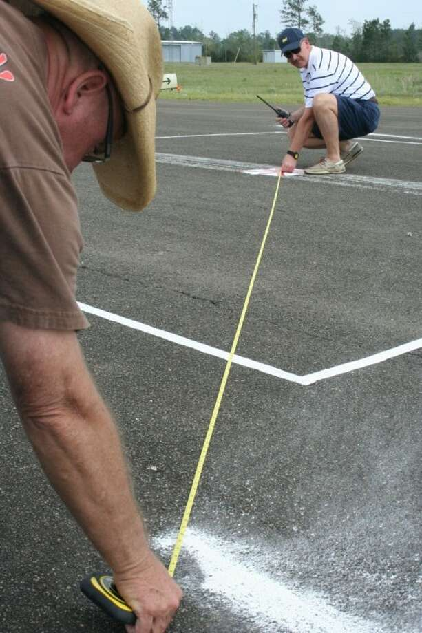 Don Fryhover (right) and Clay Dean, president and vice president of the Cleveland Aviators Aero Club (CAAC) respectively, measure the point of landing from the center of the target to determine how close the competitors came to hitting the target at a flour-bombing exercise at Cleveland Municipal Airport.