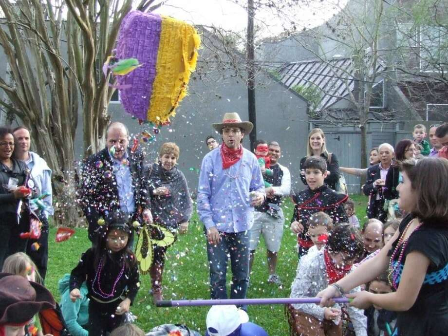 Kids scurry for candy as it falls from a Mardi Gras pinata, part of the Italian Cultural Center's Carnevale celebrations Sunday.