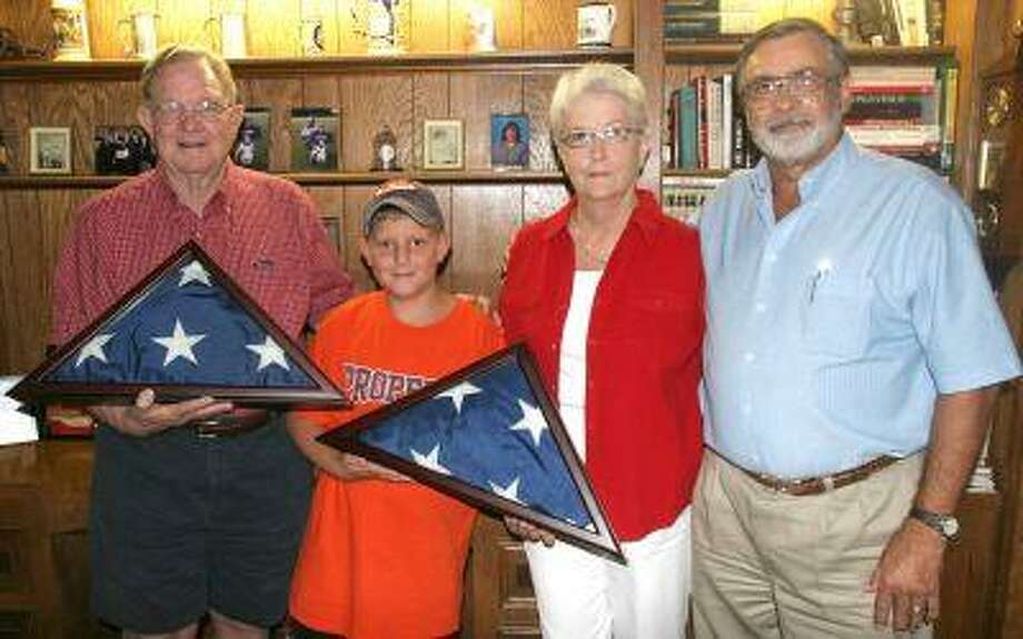 TWO FLAGS. Dayton Mayor Steve Stephens (r) presented two flags last Friday to (from left) Sonny, grandson Hunter, and Tish Richter flown in memory of her dad, J.D. McGinty, Sr. and brother Drue McGinty, both of whom served in the armed forces.