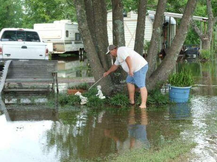 Toby Bigley cleans up his lawn in Edouard's wake. The storm dropped over 15 inches of rain on his property off FM 1942 near Crosby. Other than the torrential rain and some gusty winds, however, he said the storm was little to fret over, a sentiment echoed by many in the community.